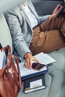 Arbeiten im taxi vertikal abgeschnittene aufnahme einer geschäftsfrau, die auf dem rücksitz im auto sitzt und benutzt