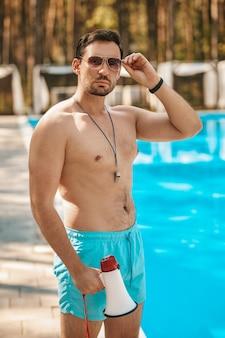 Arbeiten. männlicher rettungsschwimmer mit sonnenbrille in der nähe des öffentlichen schwimmbads