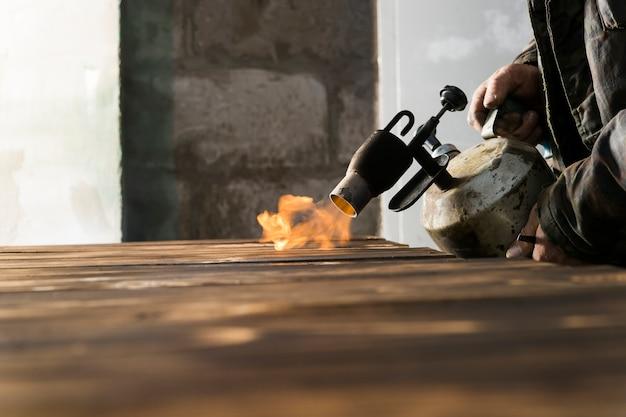 Arbeiten mit dem gasbrenner zum verbrennen von holz und zur künstlichen alterung