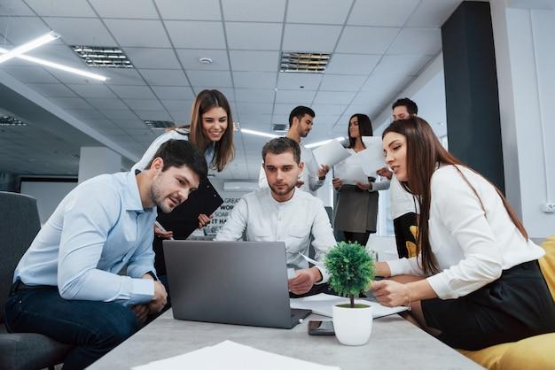 Arbeiten mit laptop. eine gruppe junger freiberufler im büro unterhält sich und lächelt