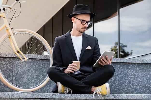 Arbeiten mit technologie außerhalb des büros. junger mann im stilvollen freizeitanzug, der am telefon im stadtgebiet spricht und neben einem pendlerfahrrad sitzt