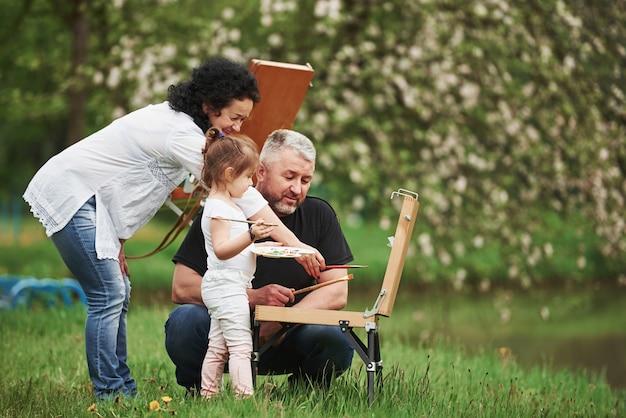 Arbeiten mit verschiedenen pinseln. großmutter und großvater haben spaß im freien mit enkelin. malkonzeption