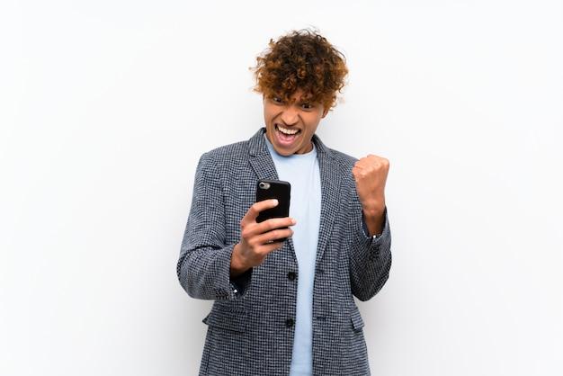 Arbeiten sie afroamerikanermann über lokalisierter weißer wand mit telefon in siegposition um