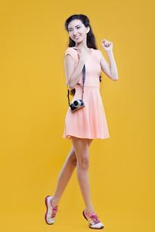 Arbeiten sie asiatischen fotografen des jungen mädchens mit kamera, porträt auf gelb um