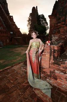 Arbeiten sie asiatisches mädchen im thailändischen traditionellen kostüm im alten tempel mit lenkradblume in der hand um