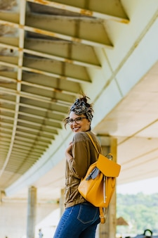 Arbeiten sie das lebensstilporträt der jungen glücklichen hübschen frau um, die draußen lächelt.