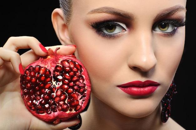 Arbeiten sie das porträt des jungen modells um, das mit rotem reifem pomegnate aufwirft.