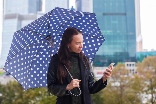 Arbeiten sie die junge frau um, die in der hand am telefon mit einem regenschirm spricht