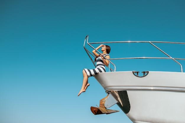 Arbeiten sie entzückende junge frau im gestreiften kleid um, das auf rand der luxusyacht sitzt und das meer während der segelreise schaut. glückliche frau, die sommerreise genießt. urlaub oder ferien