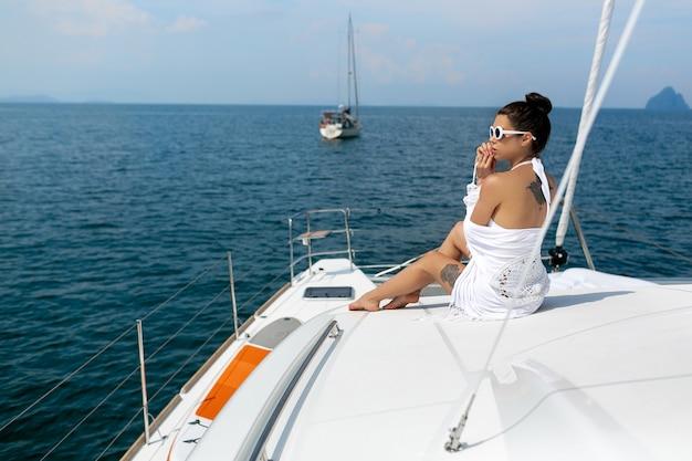 Arbeiten sie foto der entzückenden jungen frau im weißen badeanzug und im kap um, die auf rand der luxusyacht sitzen und nach dem meer während der segelreise suchen