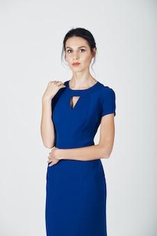 Arbeiten sie foto der jungen ausgezeichneten frau in einem blauen kleid um