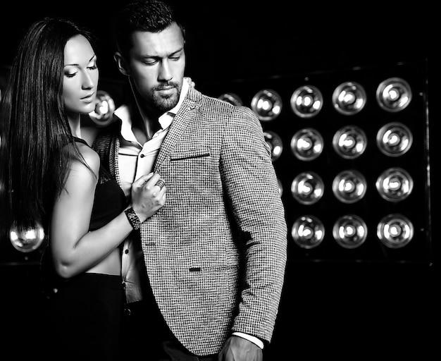 Arbeiten sie foto des hübschen eleganten mannes in der klage mit der schönen sexy frau um, die auf schwarzem studio aufwirft, beleuchtet hintergrund