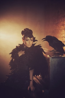 Arbeiten sie gotisches porträt eines schönen brunette mit raben in einem langen schwarzen kleid um, das von den rabenfedern gemacht wird. halloween