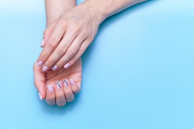 Arbeiten sie handkunstfrauen, hand mit hellem kontrastmake-up und schönen nägeln, handpflege um.