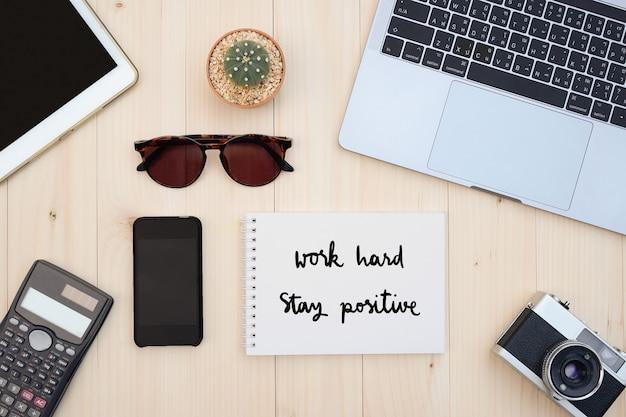 Arbeiten sie hart bleiben sie auf hölzernem schreibtischhintergrund positiv