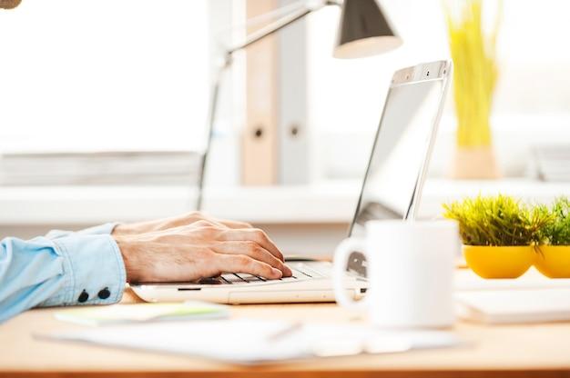 Arbeiten sie hart, um fristen einzuhalten. nahaufnahme eines jungen mannes, der am laptop arbeitet, während er an seinem arbeitsplatz sitzt