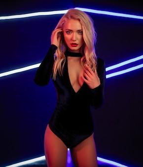 Arbeiten sie kunstfoto des eleganten modells mit neonlicht auf dem hintergrund um