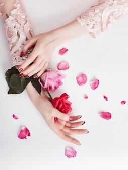 Arbeiten sie kunstporträtfrau im sommerkleid und in den blumen in ihrer hand mit einem hellen kontrastierenden make-up um. kreative schönheitsfotomädchen, die bei tisch auf einem kontrastierenden rosa hintergrund mit farbigen schatten sitzen