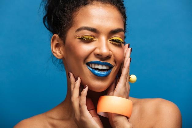 Arbeiten sie lächelnde mulattefrau mit buntem make-up und dem gelockten haar im brötchen um, das ihr hübsches gesicht berührt und auf der kamera lokalisiert, über blauer wand schaut