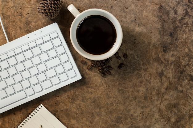 Arbeiten sie mit der tastatur und haben sie eine kaffeetasse auf dem holzboden.