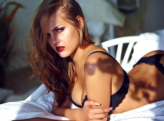 Arbeiten sie porträt des schönen sexy jungen erwachsenen blonden frauenmodells um, welches die schwarze erotische wäsche trägt, die auf bett bei sonnenuntergang liegt