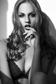 Arbeiten sie porträt des schönen sexy jungen erwachsenen blonden frauenmodells um, welches die schwarze erotische wäsche trägt, die nahe grauer wand aufwirft