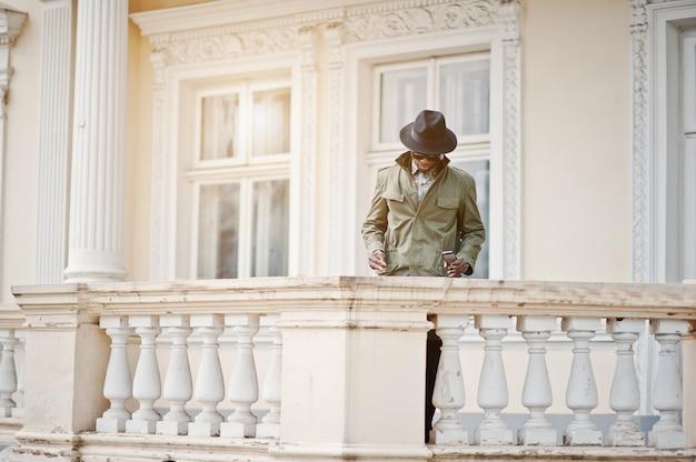 Arbeiten sie porträt des schwarzafrikanermannes auf grünem mantel und schwarzem hut, aufenthalt auf dem balkon der gelben villa um