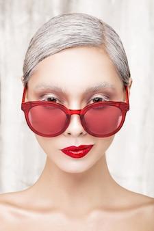 Arbeiten sie porträt eines schönen mädchens mit den roten lippen und den roten gläsern um