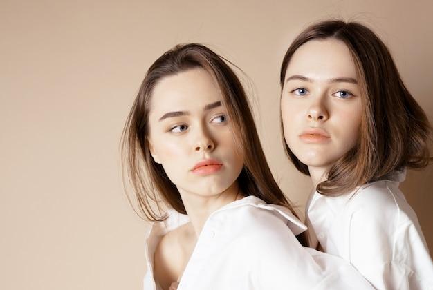 Arbeiten sie schönheitsmodelle zwei schwestern um, die schönen nackten mädchen, welche die kamera betrachten, die auf beige hintergrund lokalisiert wird