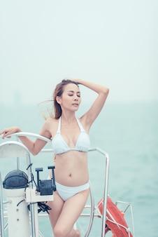 Arbeiten sie sommerfoto im freien des sexy mädchens mit dem dunklen haar im luxuriösen bikini um, der auf yacht im meer sich entspannt