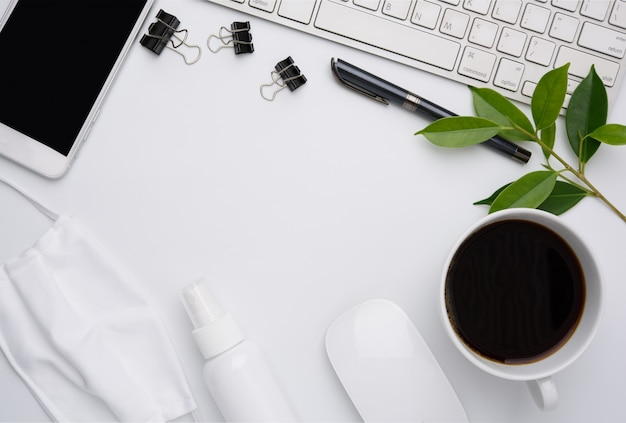 Arbeiten sie von zu hause aus konzept mit laptop, maske, kaffeetasse, stift, telefon auf weißer wand, flach liegen