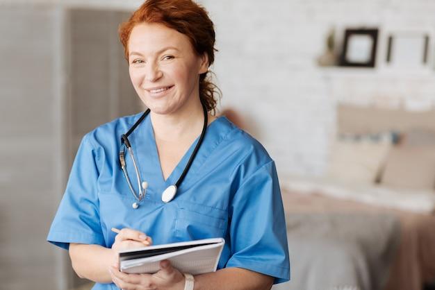 Arbeiten vor ort. sehr geehrte, weise, kompetente frau, die ihren patienten besucht und seine symptome aufschreibt, um sie zu analysieren und eine behandlung zu verschreiben