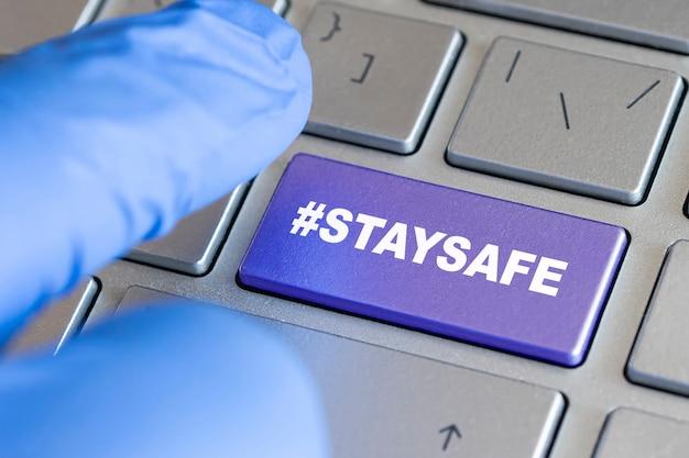 Arbeiten zu hause während des ausbruchs des corona-virus. männliche hand in einem blauen handschuh, der tastatur berührt, eingabetaste bleibt sicher. home-office-arbeit.