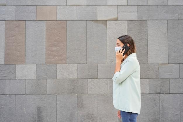 Arbeitende frau mit gesichtsmaske, die am telefon spricht.