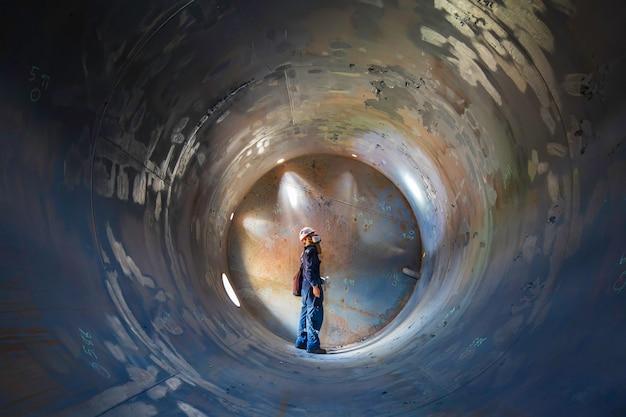 Arbeitende männliche inspektionsschweißung unterirdisch des tankausrüstungstunnels durch die verwendung der taschenlampe in der seite begrenzt.