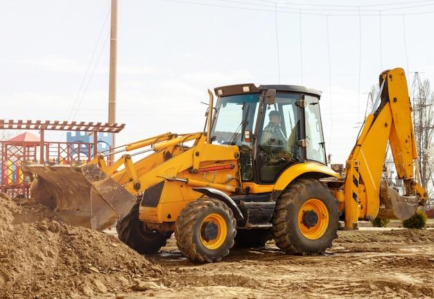 Arbeitender baggertraktor gräbt einen graben auf der baustelle