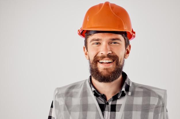Arbeitender mann im orangefarbenen schutzhelm bau professionelles studio. foto in hoher qualität