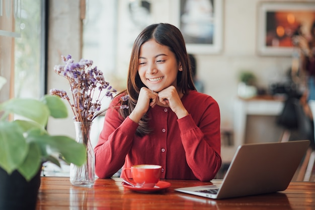 Arbeitender und trinkender kaffee des asiatischen geschäftsmädchens im café mit laptop