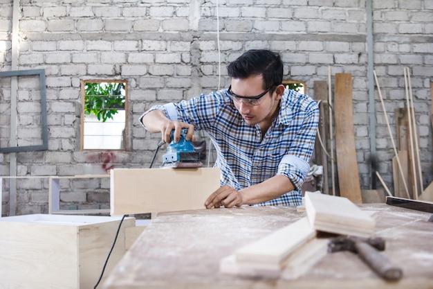 Arbeiter am tischlerarbeitsplatz, der die oberfläche der holzplatte verfeinert