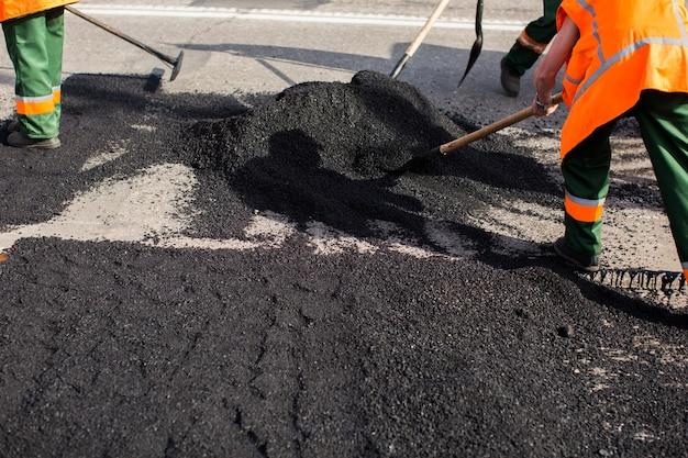 Arbeiter an der asphaltierfertigermaschine während der straßenstraßenreparaturarbeiten