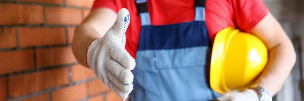 Arbeiter auf der baustelle bietet hand in schutzhandschuhen an, um die nahaufnahme des kunden zu schütteln