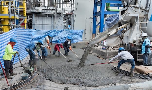 Arbeiter auf der baustelle, die betonplatte platzieren
