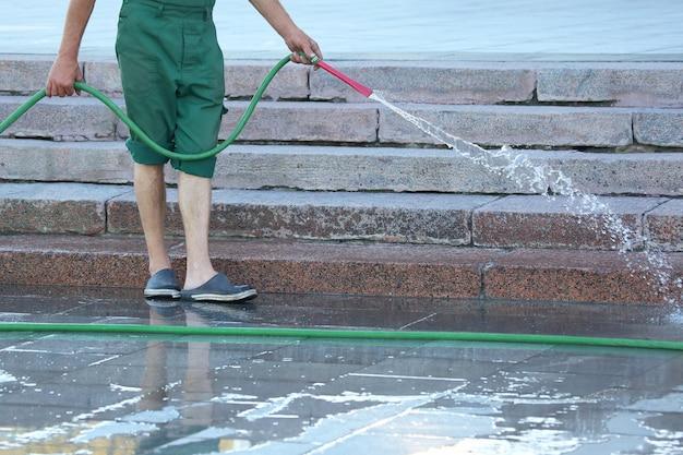 Arbeiter aus einem schlauch, der die stadtstraße bewässert