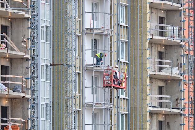 Arbeiter bauen einen balkon in einem neuen modernen wohngebäude
