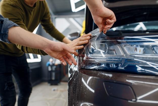 Arbeiter bringen autoschutzfolie auf den vorderen kotflügel an. anbringen einer beschichtung, die den lack des autos vor kratzern schützt. neufahrzeug in garage, tuning-vorgang