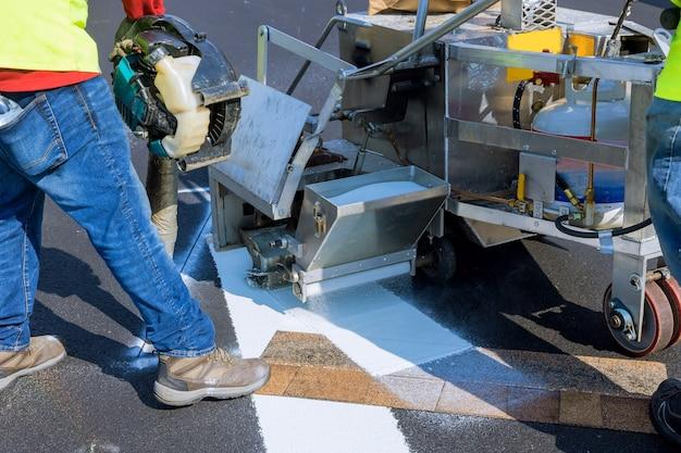 Arbeiter bringen eine straßenmarkierung mit weißer farbe auf den streifen und streuen die streifen mit einem reflektierenden pulver auf den asphalt