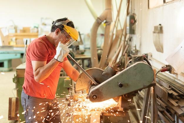 Arbeiter, der an einer maschine mit einem schutzvisier gegen funken arbeitet
