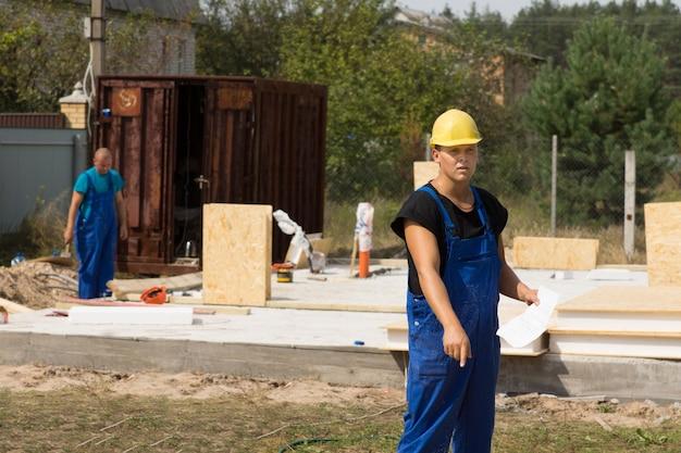 Arbeiter, der auf etwas auf dem boden zeigt, während er in seinem overall und bauarbeiterhelm steht und ein dokument auf einer baustelle für ein neues haus hält