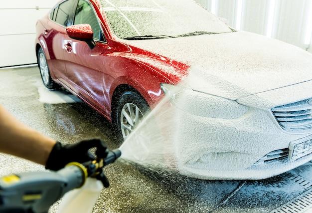 Arbeiter, der auto mit aktivem schaum auf einer autowäsche wäscht.