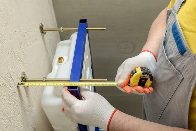 Arbeiter, der den abstand für die weitere installation des eingebauten tanks der toilette misst